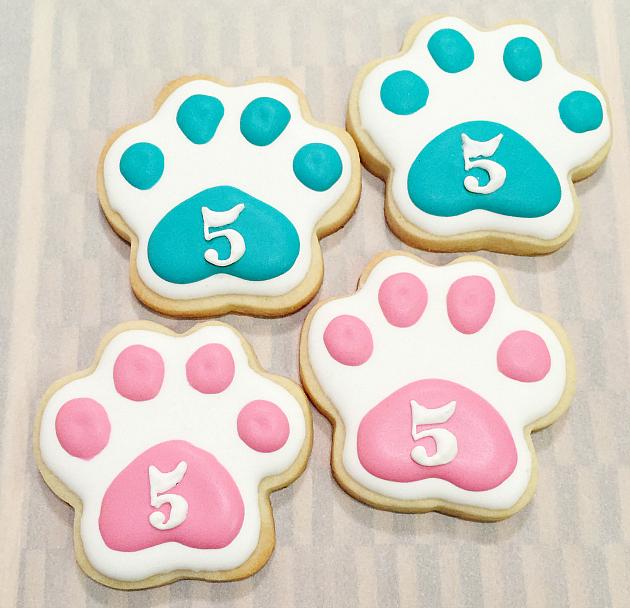 Pink and teal paw print cookies